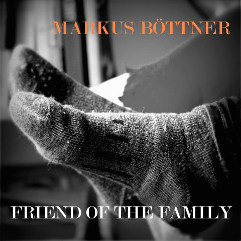 In the centre of the black-and-white image are only the feet of a young woman who is lying on a blanket on a bed with her legs crossed. The seam of her jeans and her wooly socks are clear, whilst the blanket and the background with a book shelf are blurred. In the top right of the image is the name, Markus Böttner, in orange writing; the album title Friend Of the Family, is at the bottom of the image in white.