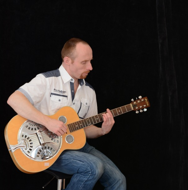 In front of a dark background is a man in his thirties, short, red-brown hair with a moustache and goatee, wearing a white and blue short-sleeve shirt and holding his Dobro resonator guitar on his lap.